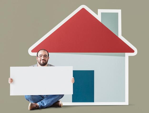 Homme tenant une affiche avec la maquette de la maison