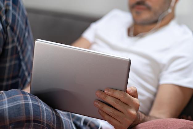 Homme tenant à l'aide d'une tablette numérique et d'un casque au lit à la maison avec pijama