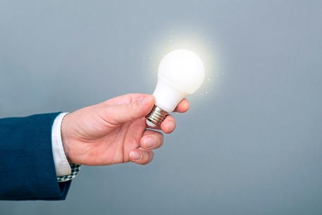 Un homme tenant une ampoule rougeoyante dans une main. image conceptuelle sur une nouvelle idée, inspiration, entreprise