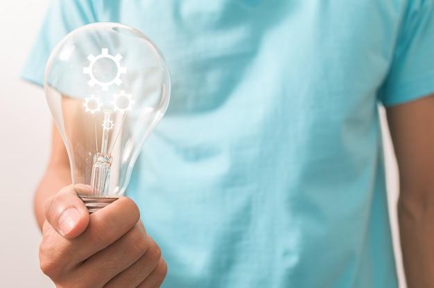 Un homme tenant une ampoule avec un symbole d'engrenage
