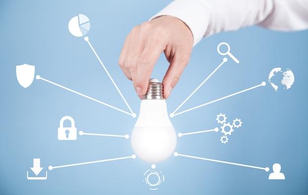 Homme tenant une ampoule. technologie et réseau innovants
