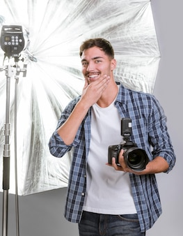Homme tenant un appareil photo professionnel