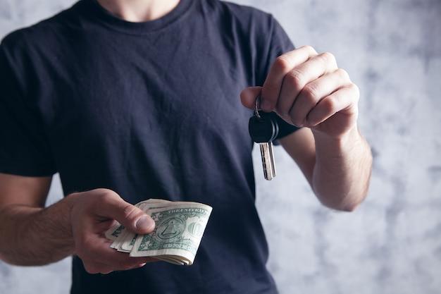 Homme tenant de l'argent et des clés de porte