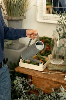 Homme tenant un arrosoir entouré de plantes