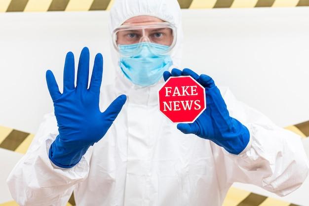 Homme tenant un badge avec de fausses nouvelles