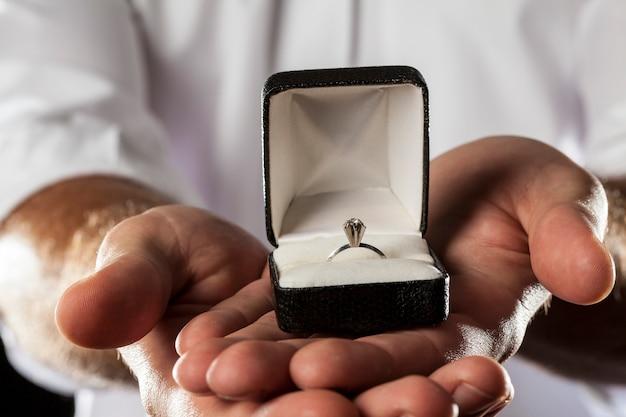 Un homme tenant une bague en diamant dans un geste de donner.