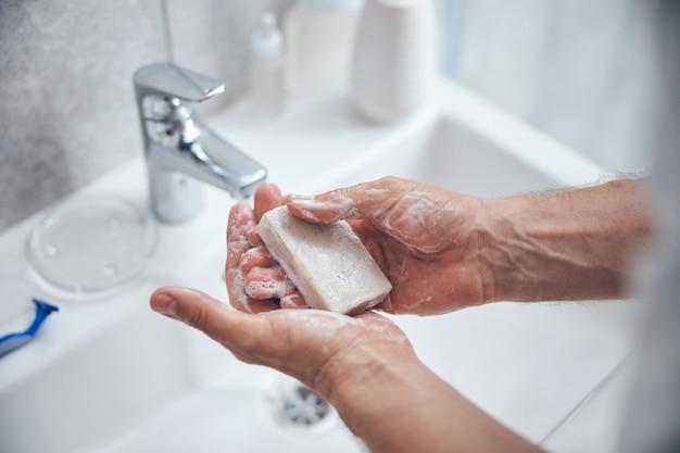 Homme tenant une barre de savon naturel sur ses paumes au-dessus de l'évier