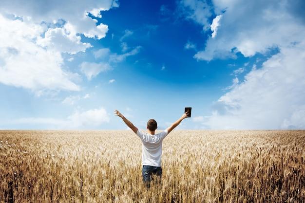 Homme tenant la bible dans un champ de blé