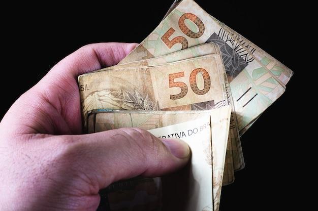 Un homme tenant un billet de 100 argent brésilien qui est le vrai brésilien sur fond noir