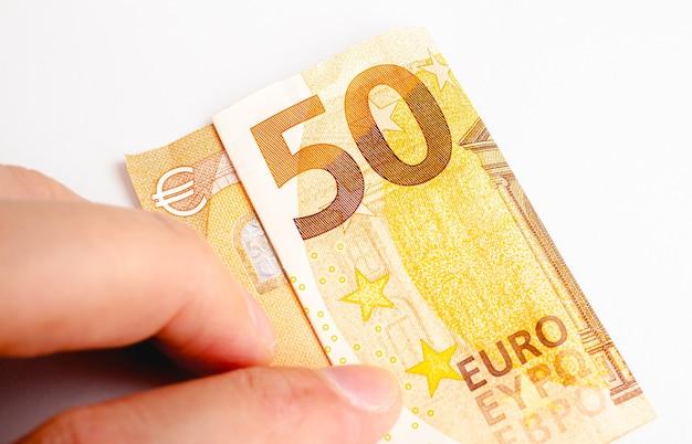 Un homme tenant un billet de 50 euros isolé sur blanc en photographie gros plan