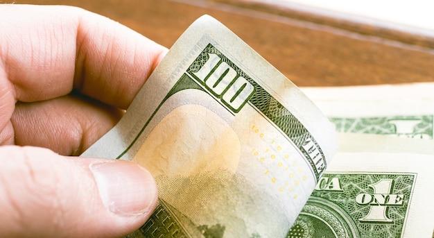 Un homme tenant un billet de cent dollars en photo en gros plan