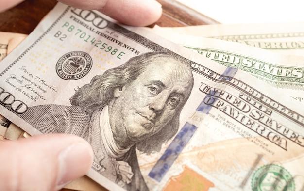 Un homme tenant un billet d'un dollar américain en photo en gros