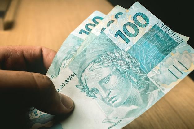 Un homme tenant des billets de 100 reais du real brésilien