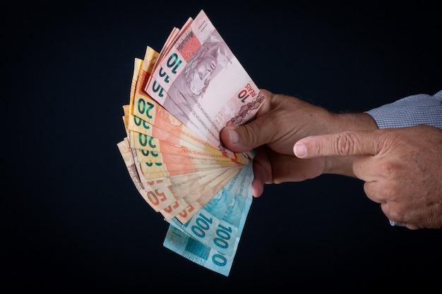 Homme tenant des billets en argent brésilien