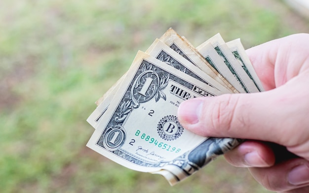 Un homme tenant des billets d'un dollar américain dans sa main