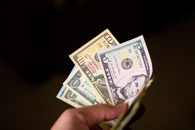 Un homme tenant des billets d'un dollar américain en forme d'éventail dans un environnement sombre