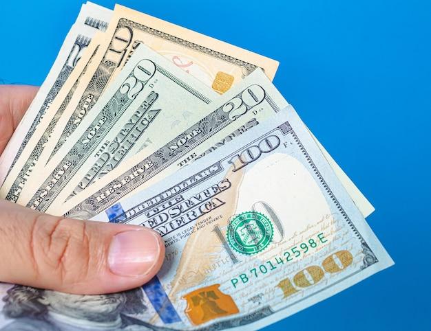 Un Homme Tenant Des Billets D'un Dollar Américain En Forme D'éventail Avec Un Fond Bleu Photo Premium