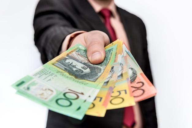 Homme tenant des billets en dollars australiens close up