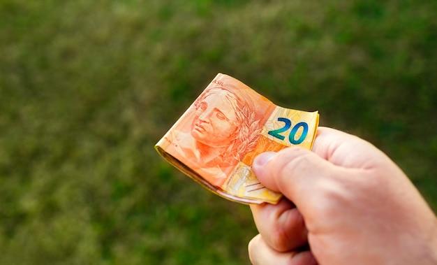 Un homme tenant des billets du real brésilien dans sa main qui sont pliés
