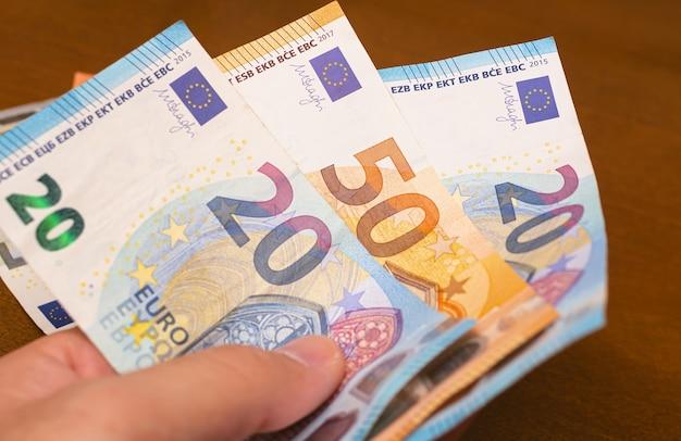 Un homme tenant des billets en euros dans sa main