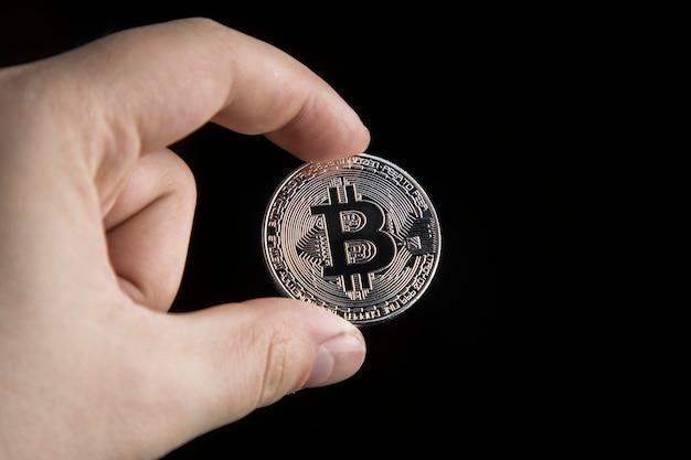 Un homme tenant un bitcoin en argent