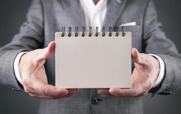 Homme tenant un bloc-notes vide. espace pour votre texte