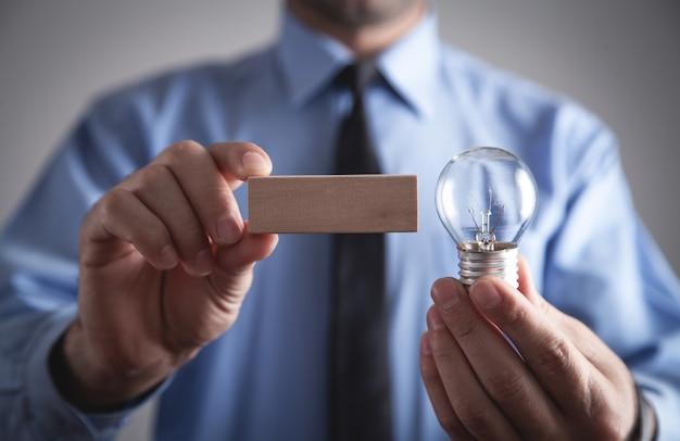 Homme tenant un bloc vide en bois avec une ampoule.