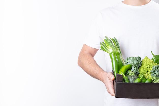Homme tenant une boîte en bois avec des légumes verts sur fond blanc avec espace de copie.