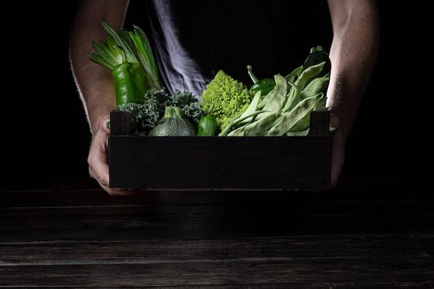 Homme tenant une boîte en bois avec des légumes verts sur fond sombre avec espace de copie.