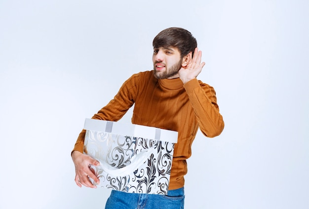 Homme tenant une boîte cadeau blanche à motifs bleus et écoutant attentivement.
