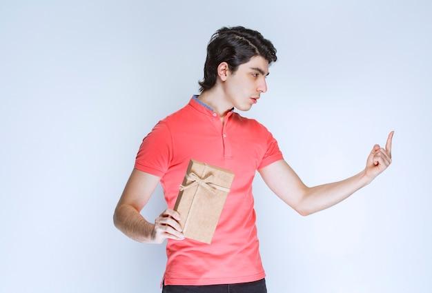 Homme tenant une boîte-cadeau en carton et pointant vers quelque part.