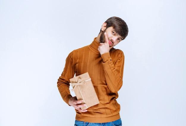 Homme tenant une boîte-cadeau en carton et semble confus et hésitant.