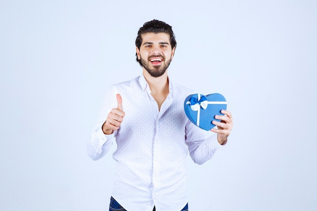 Homme tenant une boîte-cadeau en forme de coeur bleu et montrant le pouce vers le haut