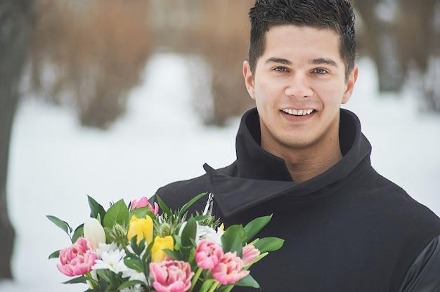 Homme tenant une boîte cadeau rouge avec un beau bouquet de tulipes roses, jaunes et blanches en fleurs et de chrysanthèmes blancs avec des feuilles vertes, à l'extérieur