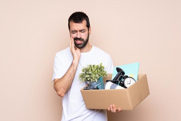 Homme tenant une boîte et emménager dans une nouvelle maison avec maux de dents
