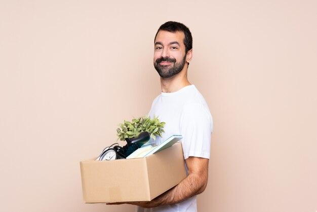 Homme tenant une boîte et se déplaçant dans la nouvelle maison avec les bras croisés et avec impatience