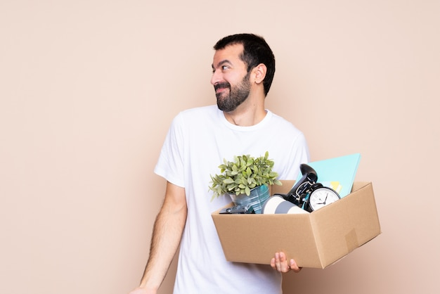 Homme tenant une boîte et se déplaçant dans la nouvelle maison faisant des doutes geste regardant côté