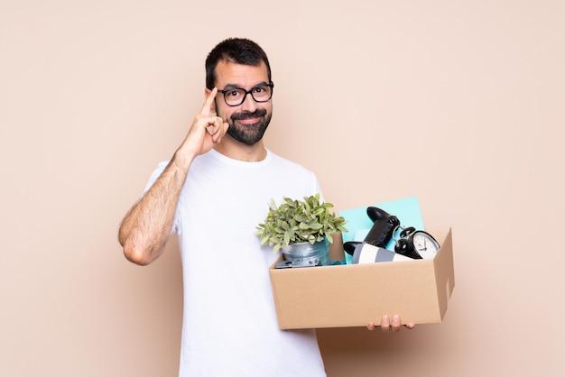 Homme tenant une boîte et se déplaçant dans la nouvelle maison sur fond isolé avec des lunettes et souriant