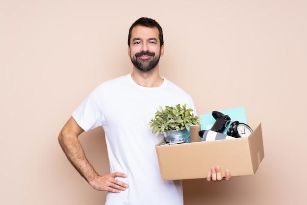 Homme tenant une boîte et se déplaçant dans la nouvelle maison posant avec les bras à la hanche et souriant