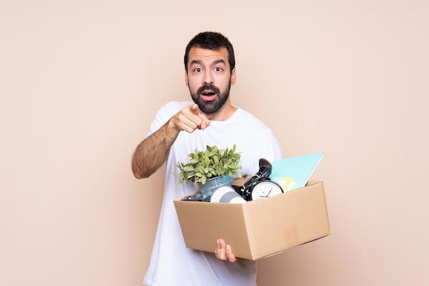 Homme tenant une boîte et se déplaçant dans la nouvelle maison surpris et pointant devant