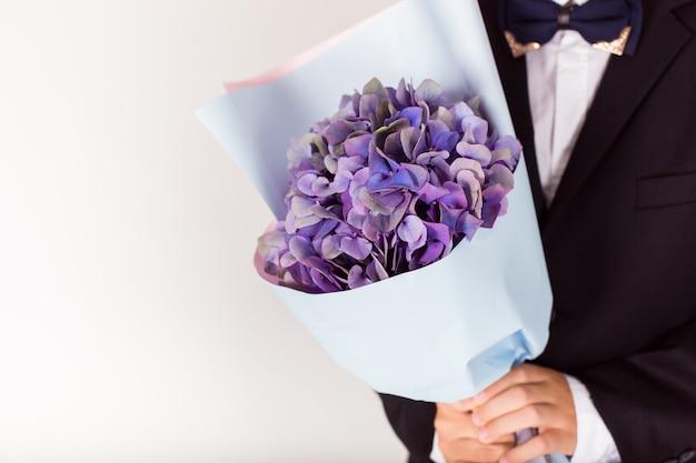 Homme tenant un bouquet de fleurs violettes