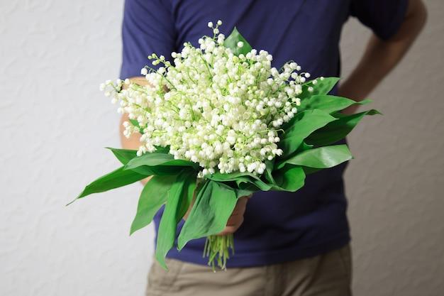 Un homme tenant un bouquet de lis de la vallée pour les femmes. un homme propose.