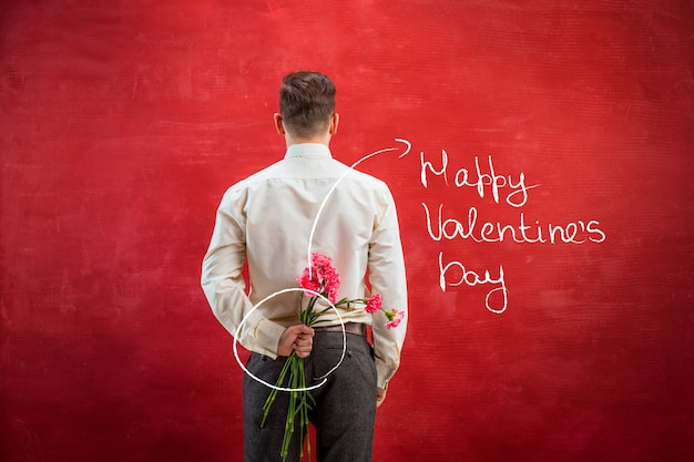 Homme tenant un bouquet d'oeillets derrière le dos sur fond de studio rouge. le concept de la saint-valentin heureuse