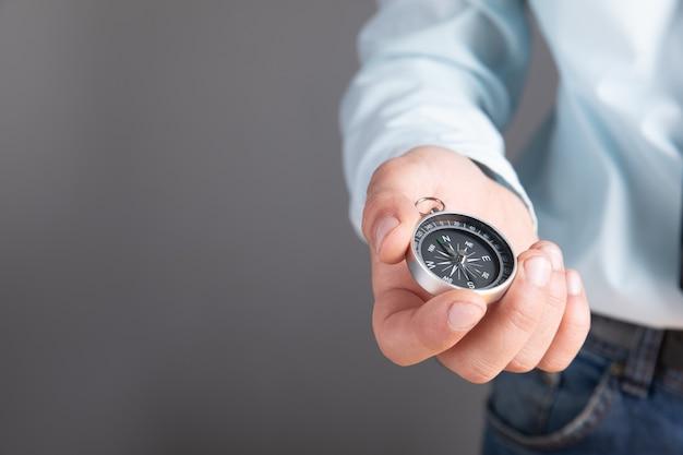 Homme tenant une boussole à la main sur une surface grise