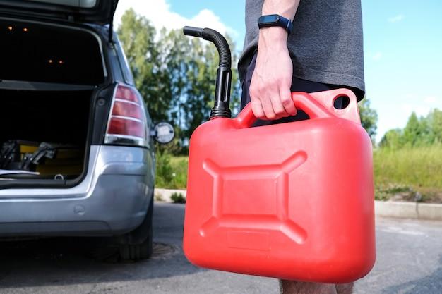Homme tenant une bouteille de gaz rouge