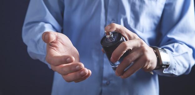 Homme tenant une bouteille de parfum.