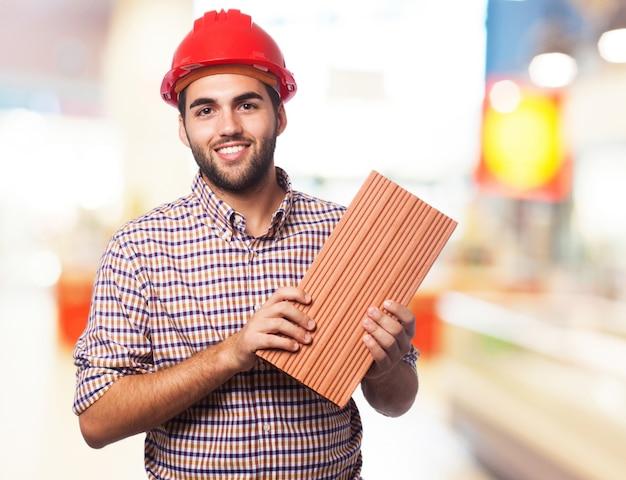 Homme tenant une brique
