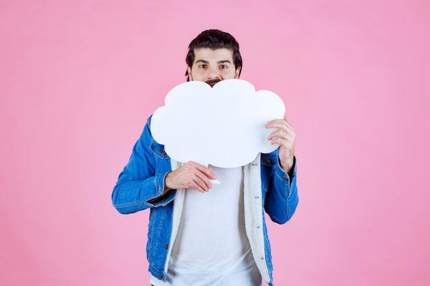 Homme tenant une bulle de dialogue vide en forme de nuage et s'amusant.