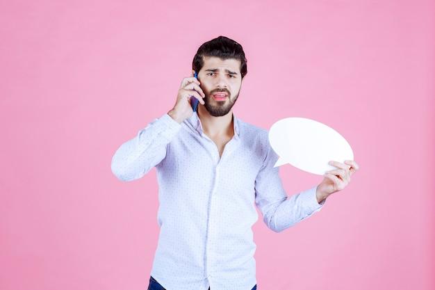 Homme tenant une bulle ovale et parlant au téléphone.