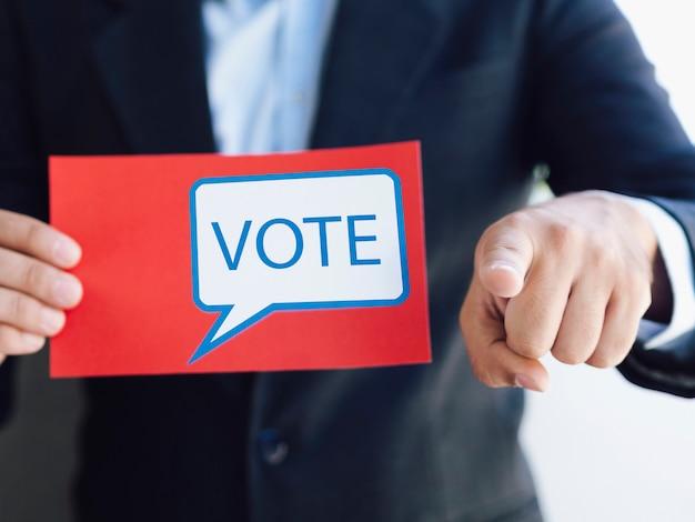Homme tenant un bulletin de vote et pointant vers la caméra